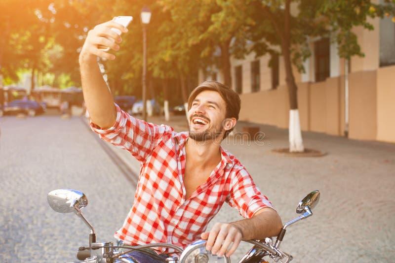 Jeune homme s'asseyant sur le scooter faisant la photo de selfie image libre de droits