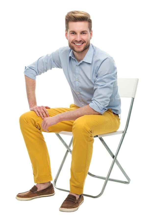 Jeune homme s'asseyant sur une chaise photo libre de droits