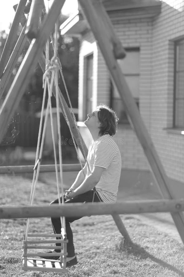 Jeune homme s'asseyant sur une oscillation images stock