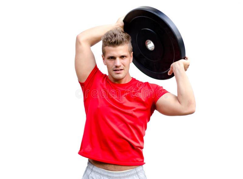 Jeune homme s'exerçant avec le grand poids, d'isolement sur le blanc photos stock
