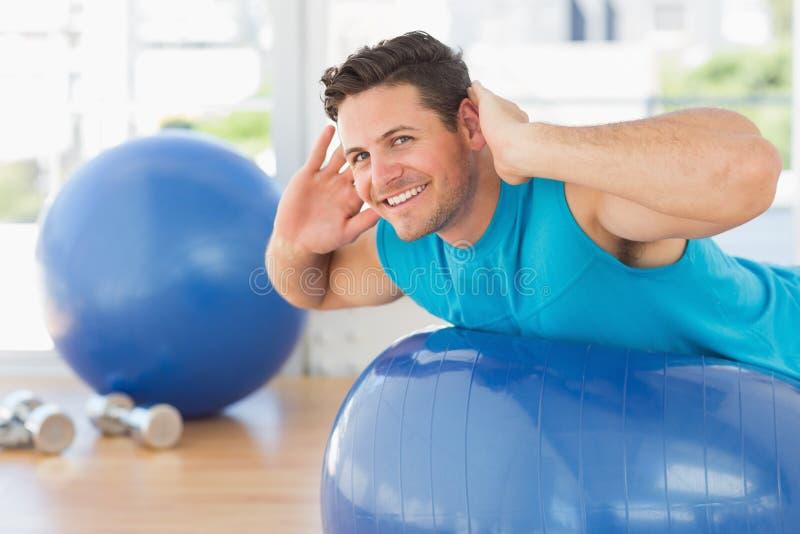 Jeune homme s'exerçant sur la boule de forme physique au gymnase photographie stock libre de droits