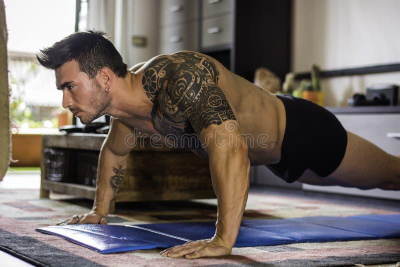 Jeune homme s'exerçant sur son plancher de salon photos stock
