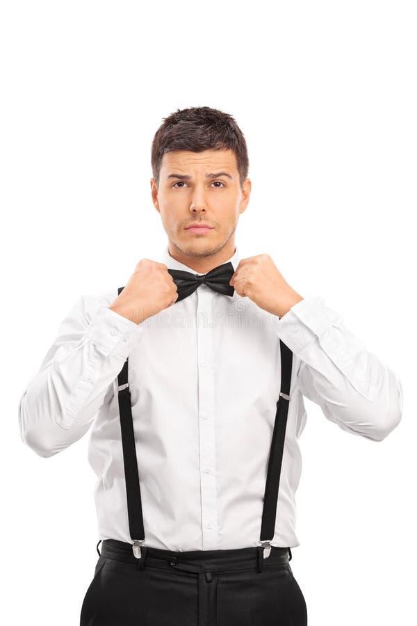 Jeune homme sûr ajustant son noeud papillon photos libres de droits