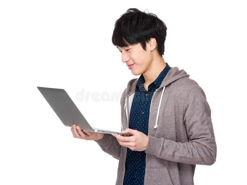 Jeune homme sûr avec la position d'ordinateur portable image libre de droits
