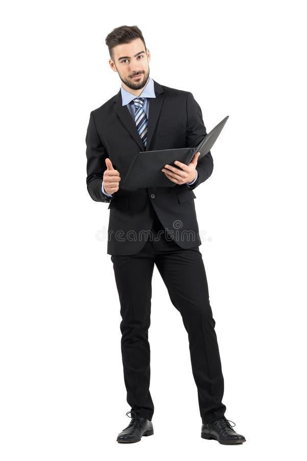 Jeune homme sûr d'affaires tenant le dossier de document avec le pouce vers le haut du geste photos libres de droits