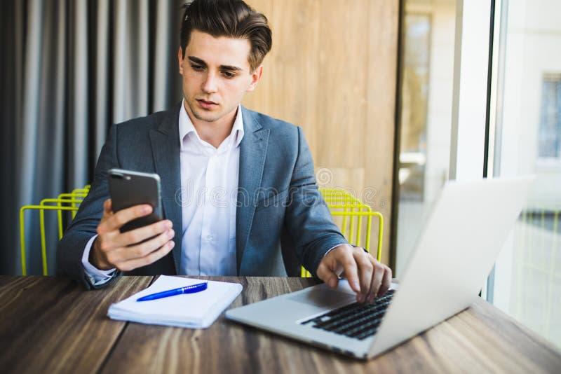 Jeune homme sûr dans la tenue de détente futée tenant le téléphone intelligent et le regardant tout en se reposant à son lieu de  image stock