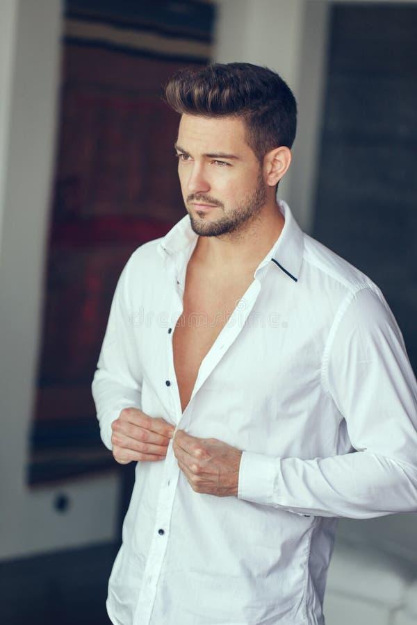 Jeune homme sûr riche boutonnant la chemise photographie stock libre de droits