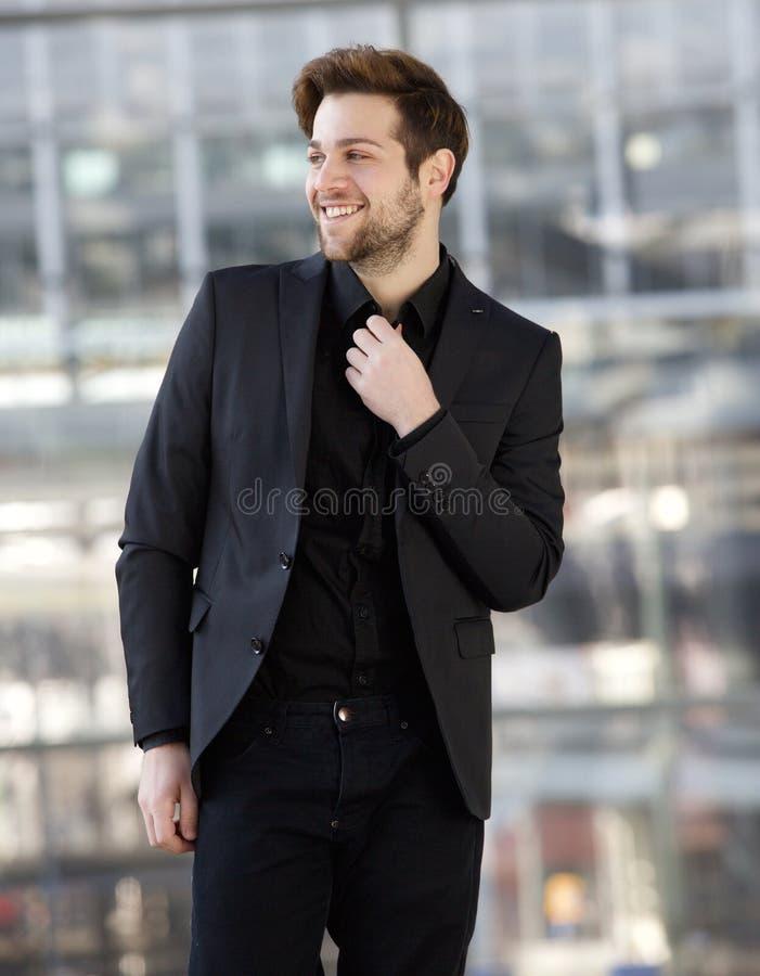 Jeune homme sûr souriant avec les vêtements noirs photos stock