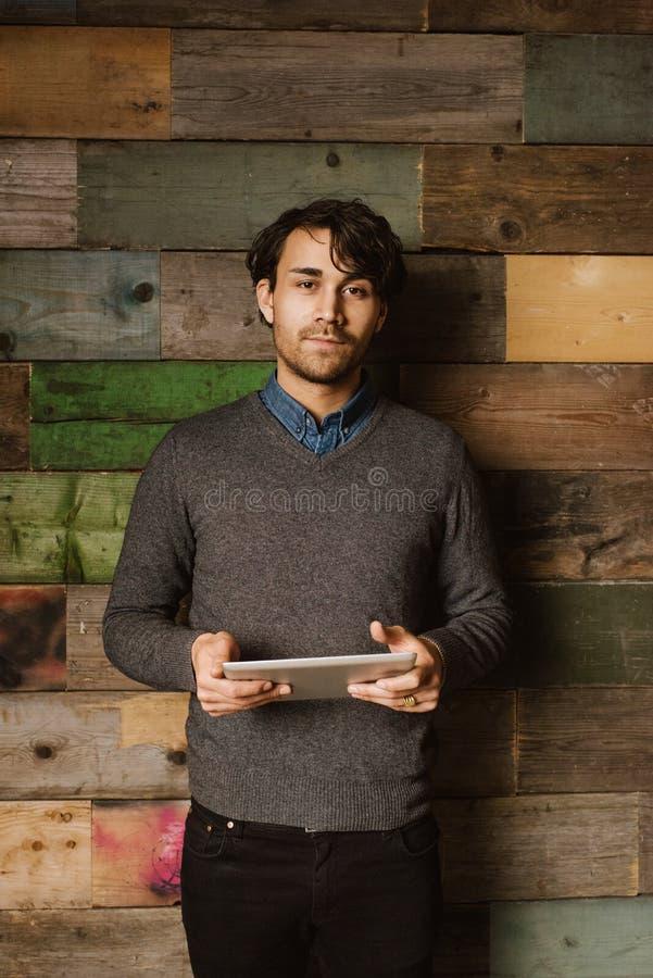 Jeune homme sûr tenant un comprimé numérique dans le bureau images libres de droits