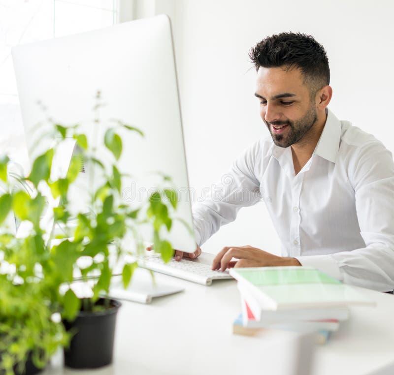 Jeune homme sûr travaillant dans le bureau moderne photos stock