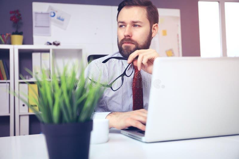 Jeune homme sûr travaillant sur l'ordinateur portable tout en se reposant à son lieu de travail dans le bureau photographie stock libre de droits