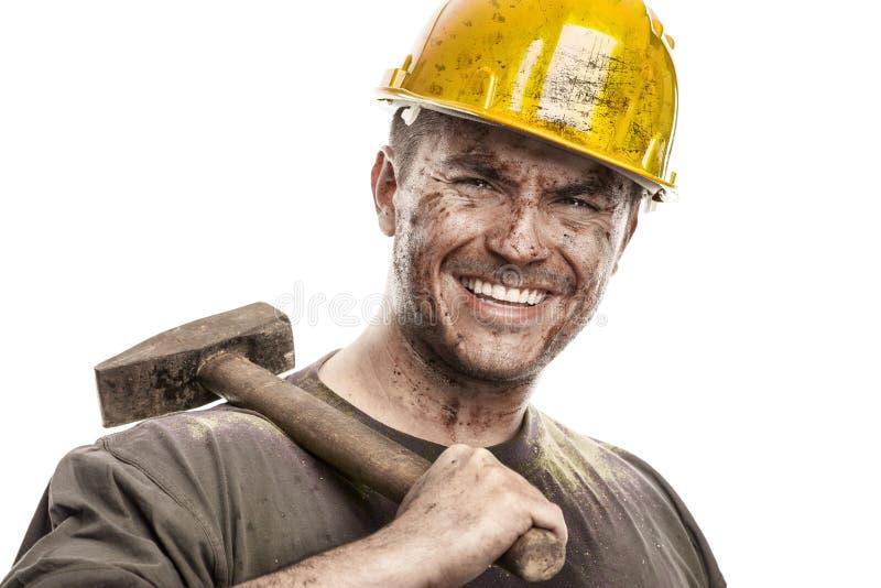 Jeune homme sale de travailleur avec le casque de casque antichoc tenant un marteau photographie stock