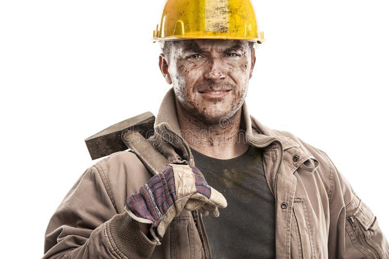 Jeune homme sale de travailleur avec le casque de casque antichoc tenant un marteau a photos libres de droits
