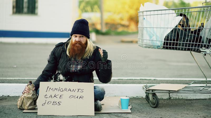 Jeune homme sans abri de renversement fâché avec le carton se reposant près du caddie et de l'alcool de boissons au jour froid en photos libres de droits