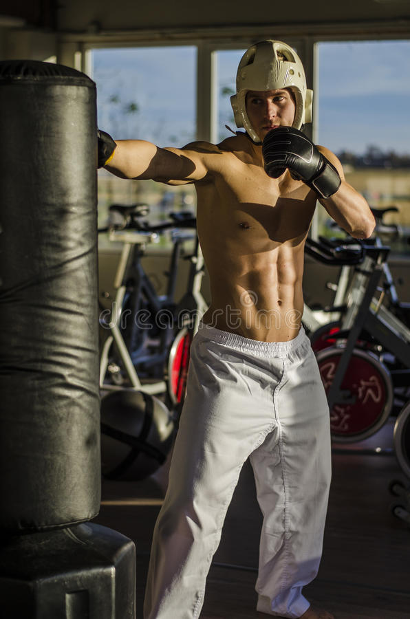 Jeune homme sans chemise à l'aide du sac de sable photographie stock