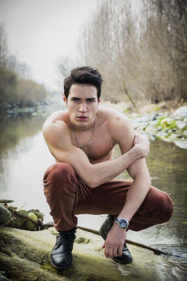 Jeune homme sans chemise d'ajustement bel à côté d'étang ou de rivière d'eau image stock