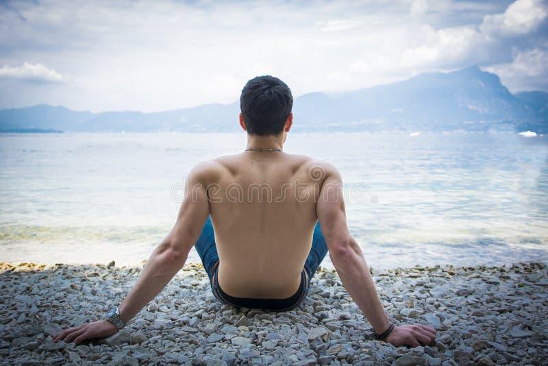 Jeune homme sans chemise musculaire sur le lac dans un ensoleillé photos stock