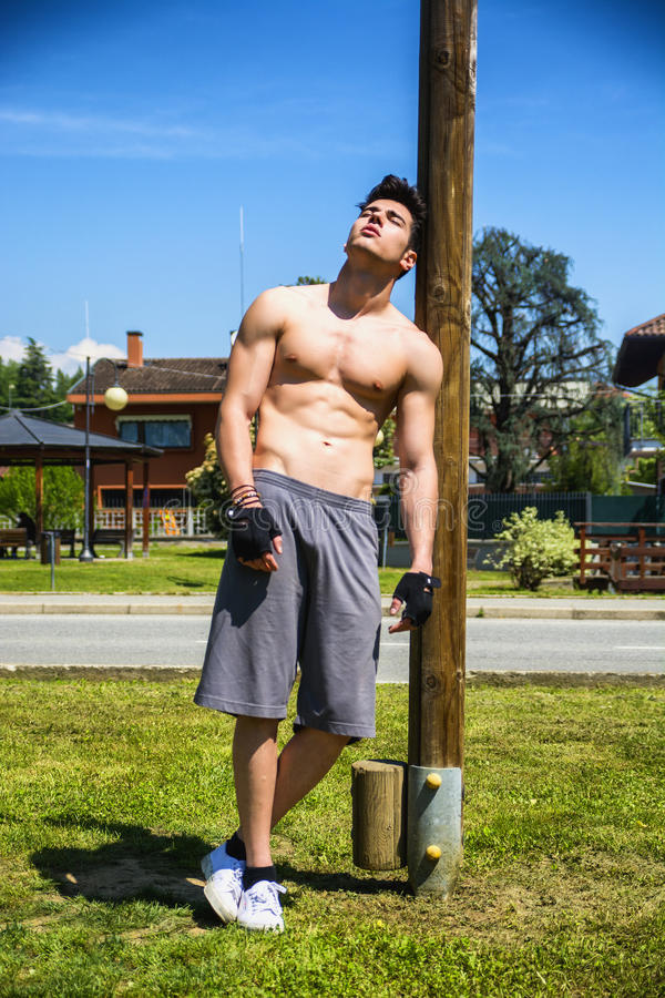 Jeune homme sans chemise se reposant après la séance d'entraînement extérieure images stock