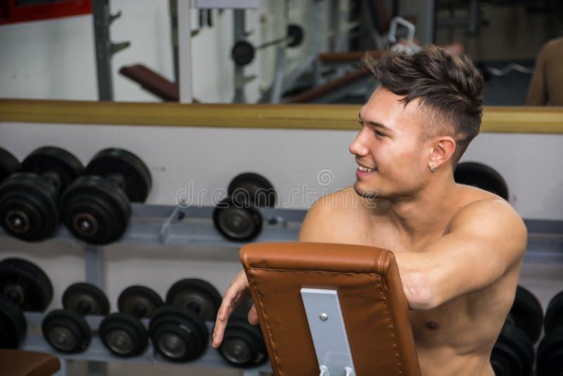 Jeune homme sans chemise se reposant dans le gymnase pendant la séance d'entraînement photos stock