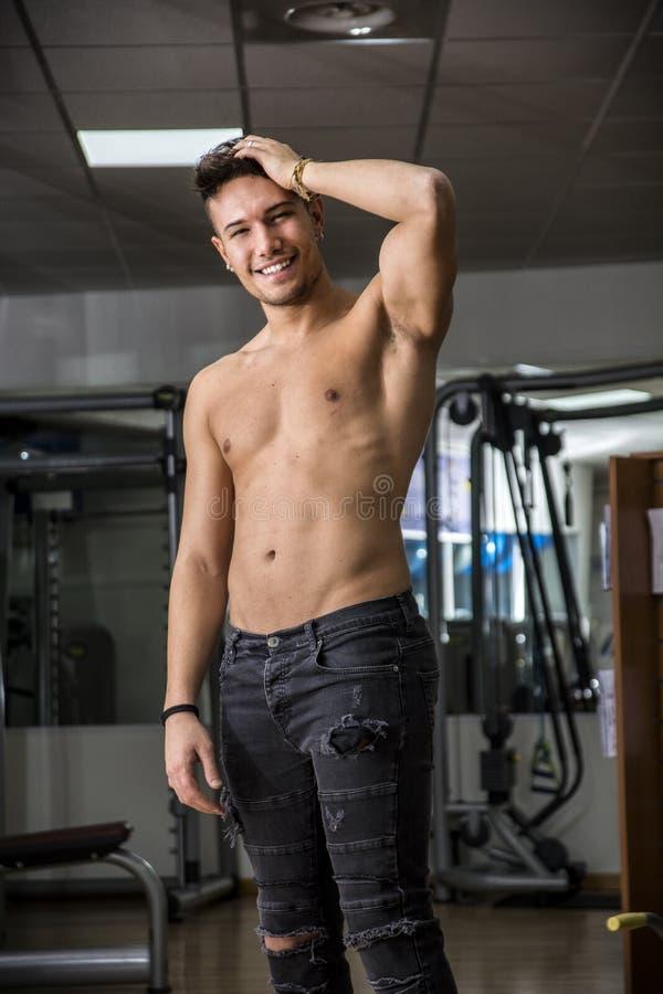 Jeune homme sans chemise se reposant dans le gymnase pendant la séance d'entraînement images libres de droits