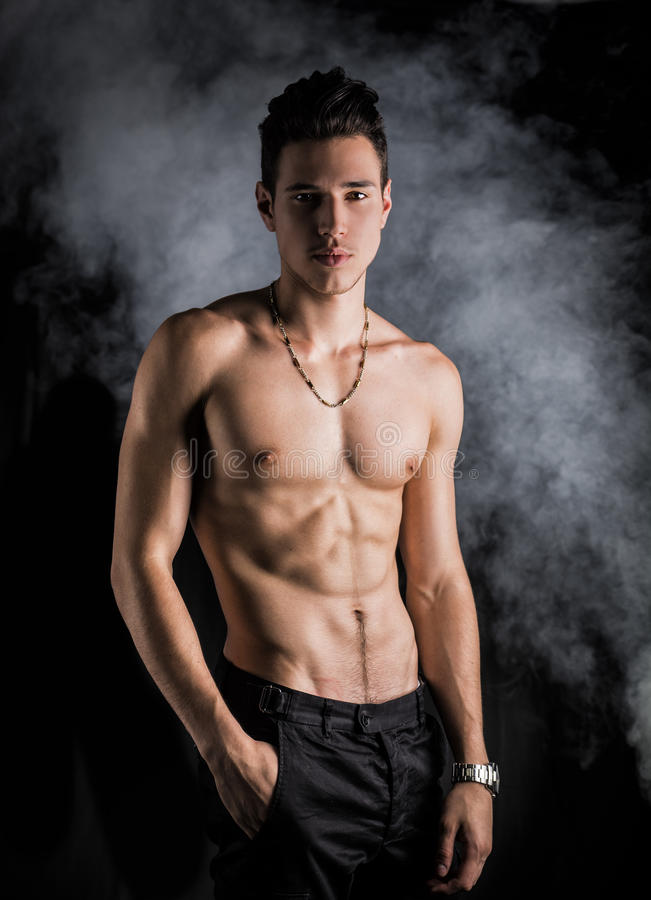 Jeune homme sans chemise sportif maigre se tenant sur le fond foncé image libre de droits