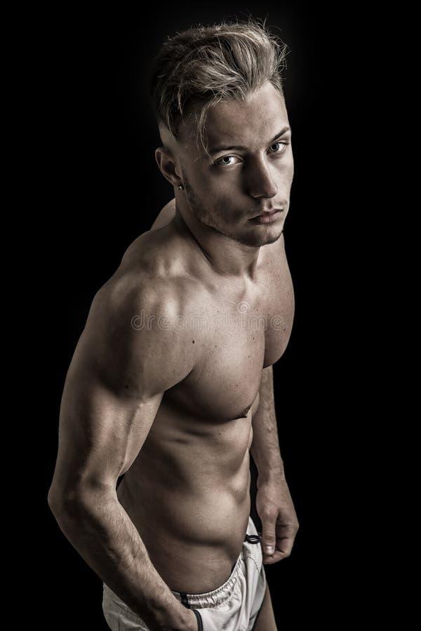 Jeune homme sans chemise sportif maigre se tenant sur le fond foncé images libres de droits