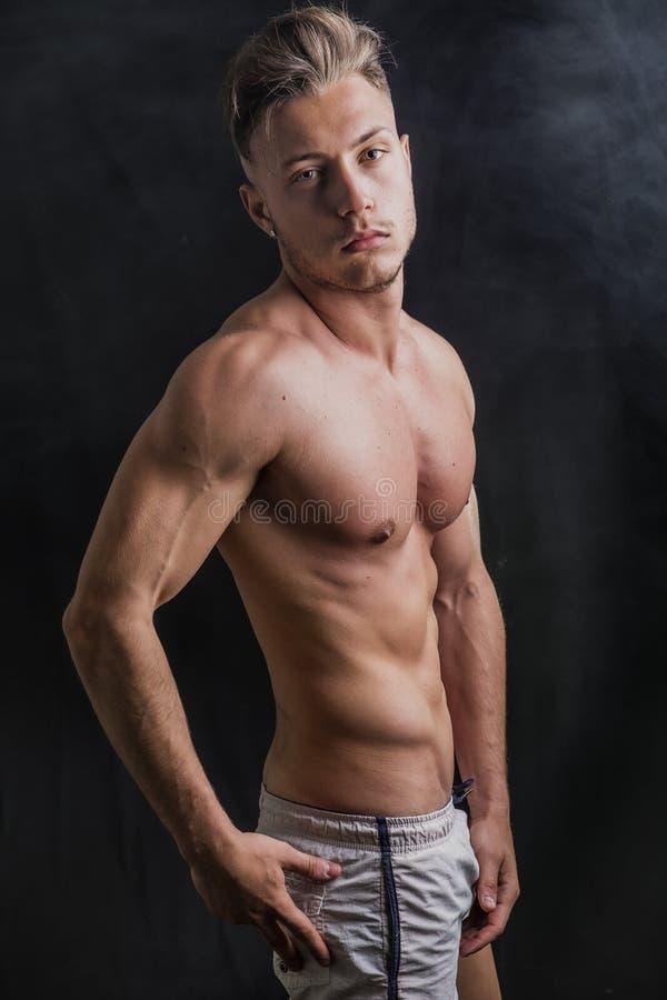 Jeune homme sans chemise sportif maigre se tenant sur le fond foncé photos libres de droits