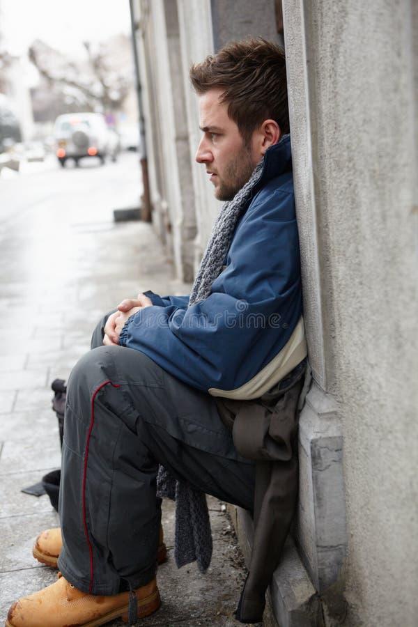 Jeune homme sans foyer priant dans la rue photo stock