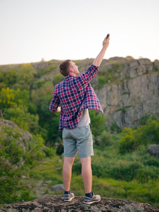 Jeune homme sans l'Internet sur un fond naturel Roches s'élevantes de voyageur pour un meilleur concept de connexion Copiez l'esp photographie stock libre de droits