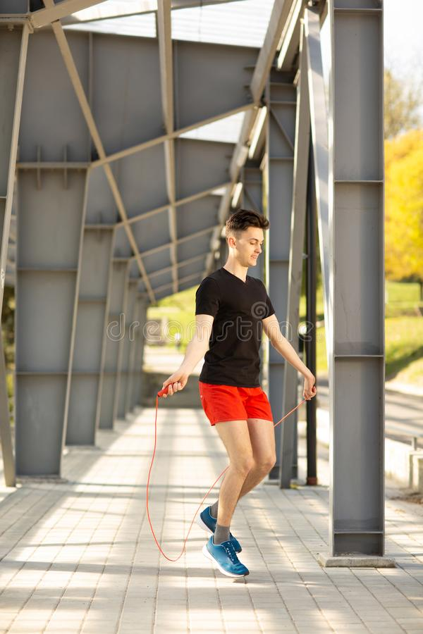 Jeune homme sautant avec la corde de saut dehors Concept d'exercice et de mode de vie images stock