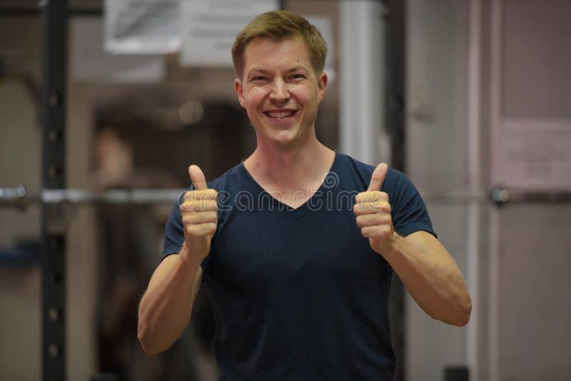 Jeune homme scandinave heureux souriant et renonçant à des pouces au gymnase photos stock