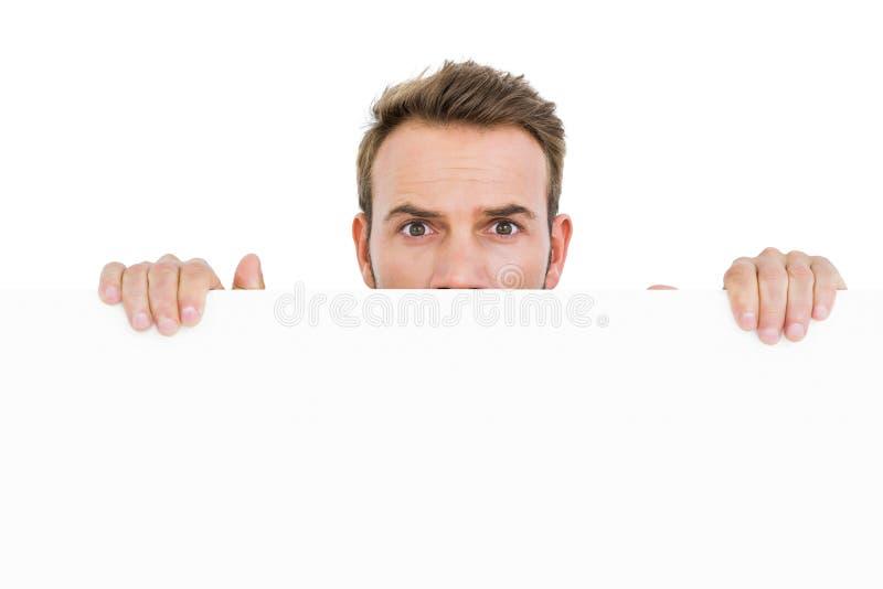 Jeune homme se cachant derrière le conseil blanc photo stock