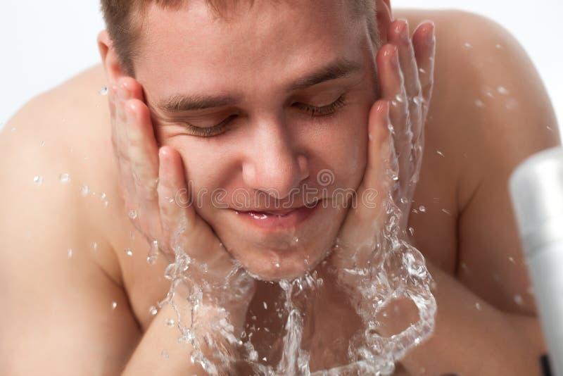 Jeune homme se lavant le visage image libre de droits