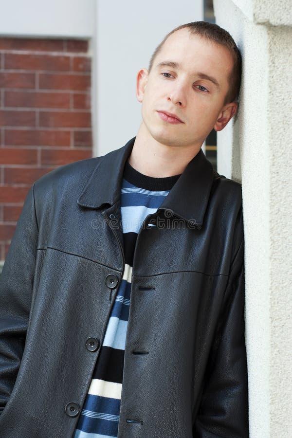 Jeune homme se penchant contre le mur photographie stock libre de droits