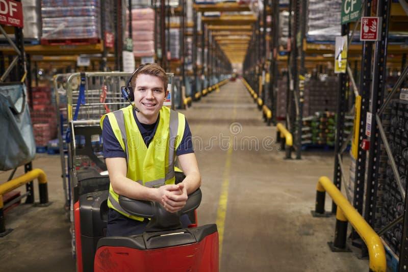 Jeune homme se penchant sur le tracteur de remorquage dans l'entrepôt de distribution photos stock