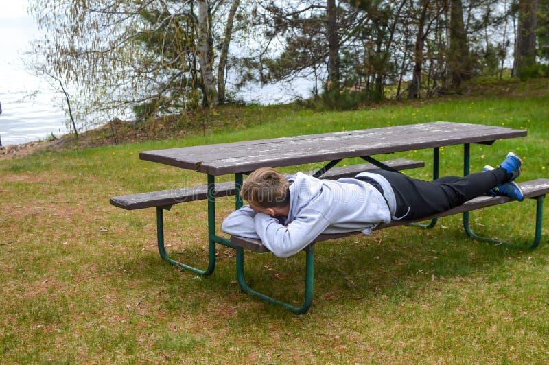 Jeune homme se reposant sur le banc de parc par le lac images stock