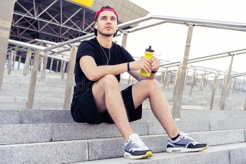 Jeune homme se reposant sur les escaliers après fonctionnement photo libre de droits