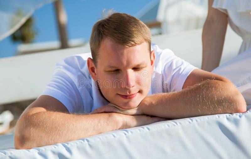 Jeune homme se reposant sur une plage photographie stock libre de droits