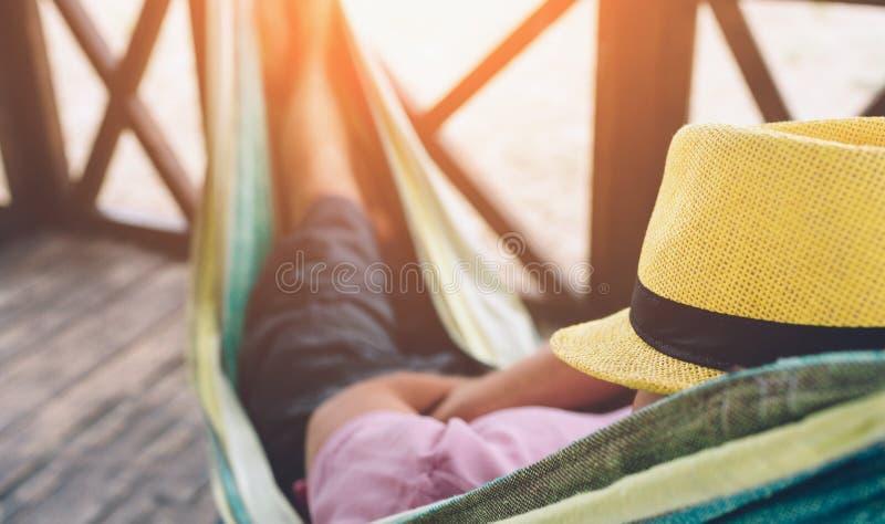 Jeune homme se situant dans l'hamac à la plage ensoleillée par l'océan et le sommeil Il se tiennent a eu sur le visage Refroidiss photographie stock libre de droits
