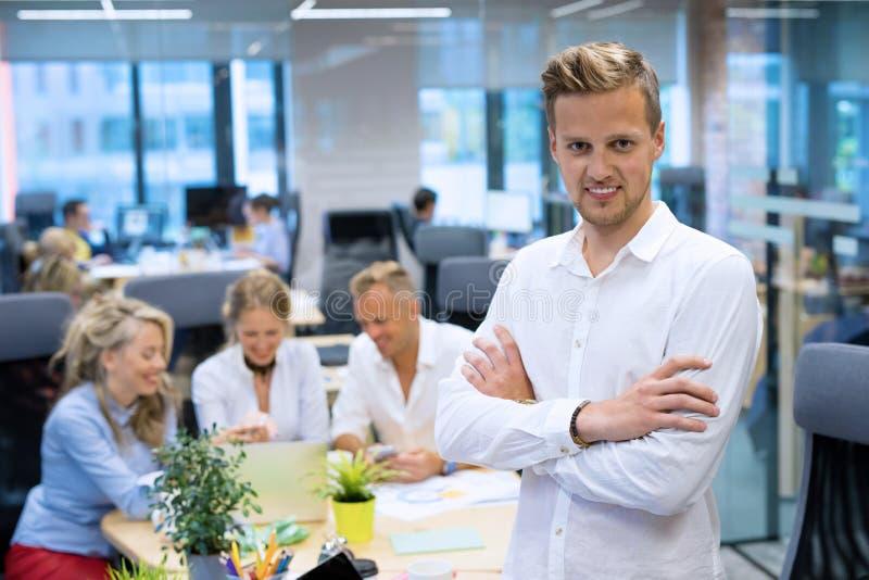 Jeune homme se tenant dans le bureau photo libre de droits