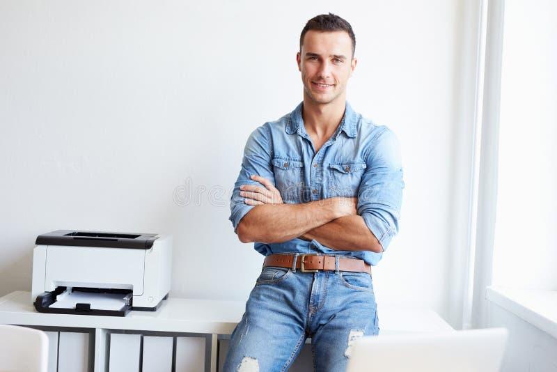Jeune homme se tenant dans le bureau avec les bras croisés photo stock
