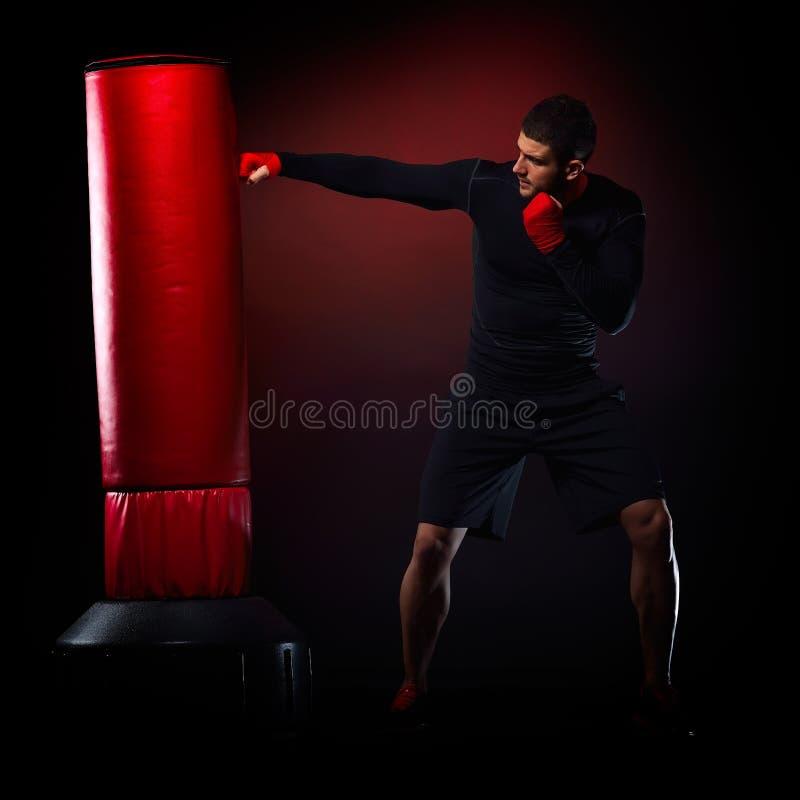Download Jeune Homme Se Tenant S'exerçant Avec Le Sac De Boxe Photo stock - Image du exercer, boxe: 56483326