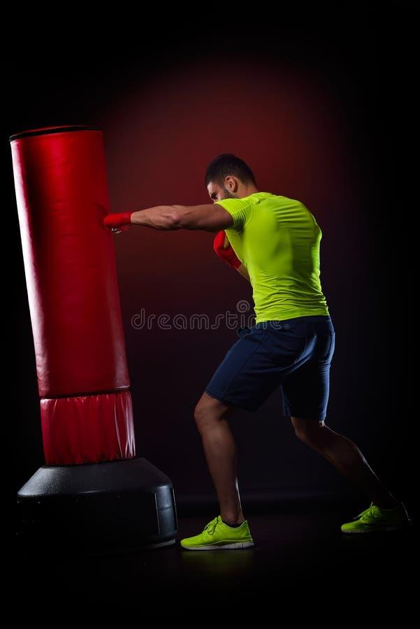 Download Jeune Homme Se Tenant S'exerçant Avec Le Sac De Boxe Photo stock - Image du muscles, cadre: 56483510