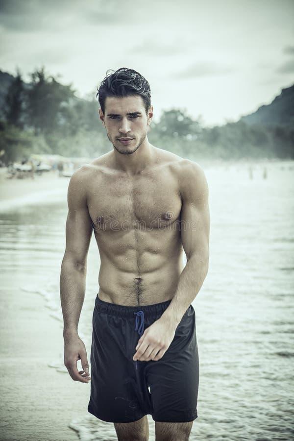 Jeune homme se tenant sur le bord de l'océan photo stock