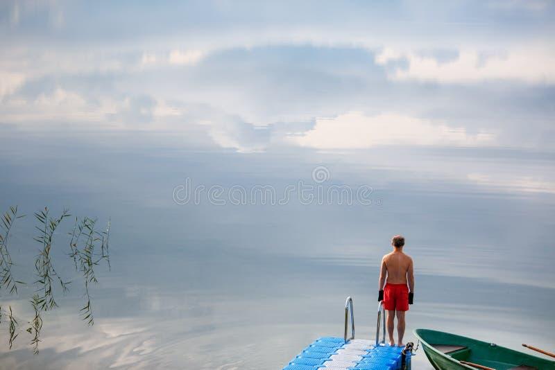 Jeune homme seul se tenant sur la jetée dans le lac Lever de soleil au-dessus du lac dans le village images stock