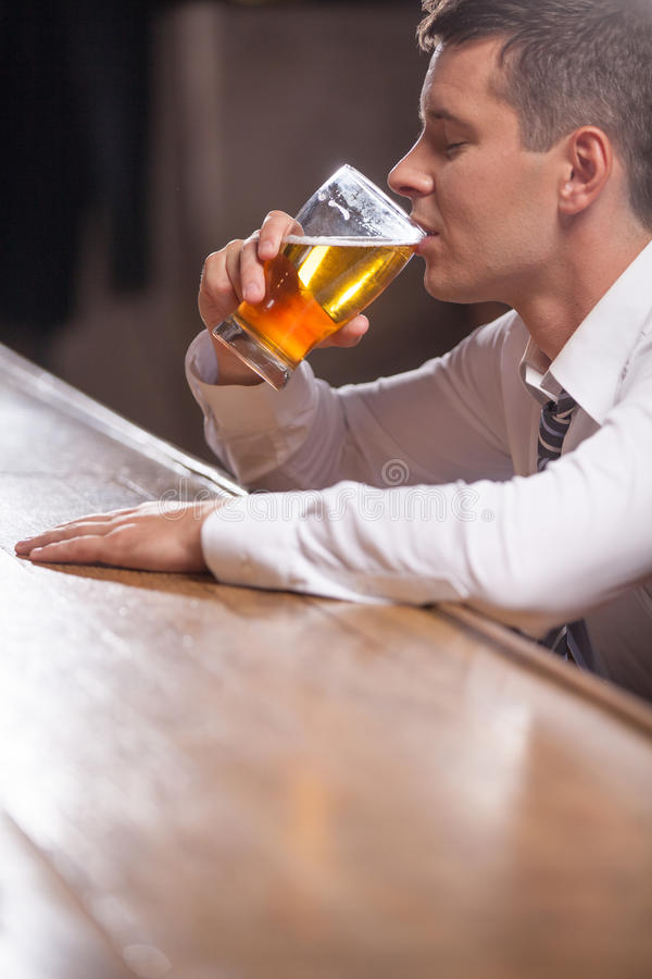 Jeune homme seul seul buvant au bar photo stock