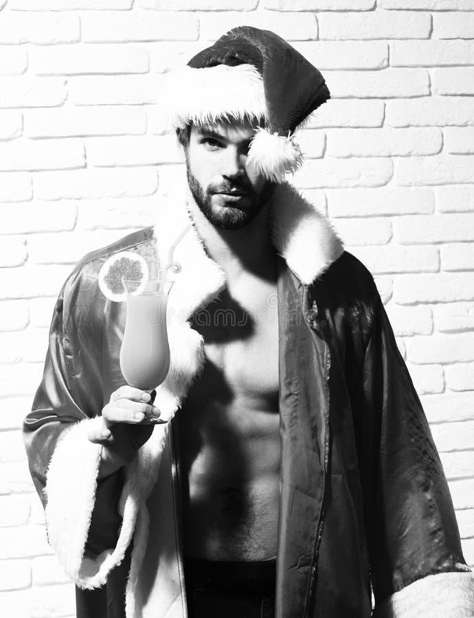 Jeune homme sexy barbu bel de Noël avec la barbe élégante dans le chapeau et le manteau rouges du père noël avec le torse nu musc image libre de droits