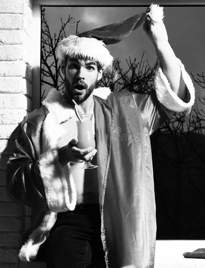 Jeune homme sexy barbu bel de Noël avec la barbe élégante dans le chapeau et le manteau rouges du père noël avec le torse nu musc photos stock