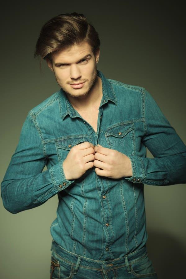 Jeune homme sexy de mode déboutonnant sa chemise de jeans image libre de droits