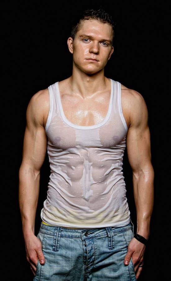 Jeune homme sexy musculaire dans le T-shirt humide blanc image stock